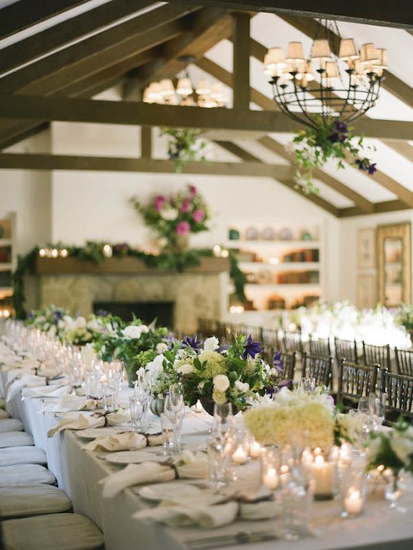 beautiful white table linens with green, white, and pops of purple in the arrangements