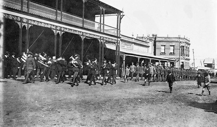 Welcome Home Parade, Nhill, 1919. The 24th battalion marching along Victoria street, Nhill. A band leads the procession and the Union Hotel is in the background with a fruiterer, R. Edwards, Boot Palace and the old Commercial Banking Company.