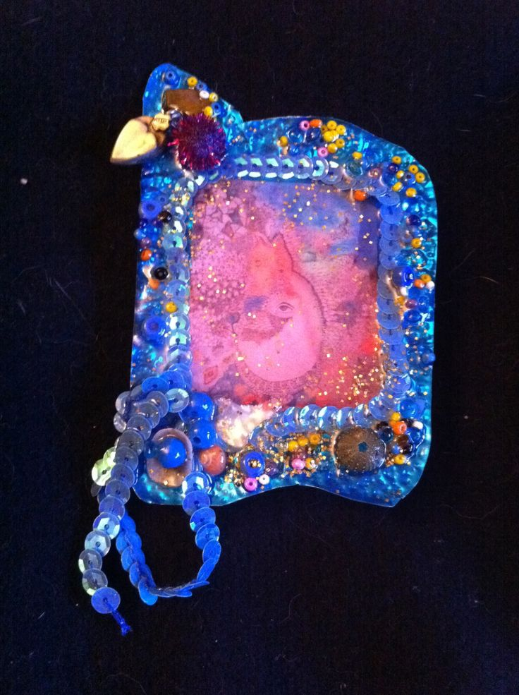 Metal jewellery with shells, beads, ribbon and image under resin