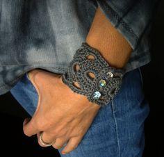 Gehäkeltes Armband in Anthrazit.   Verschlossen wird es mit drei irisierend schimmernden Glasschliffperlen.