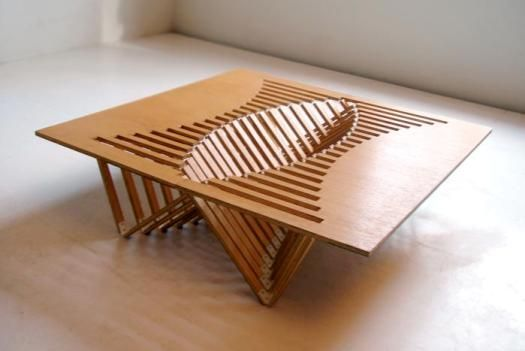 """The creative 'Rising Table' easily transforms from a single, flat piece of wood into a functional item of furniture with a beautiful latticework of supporting legs. The inspired creation by designer Robert van Embricqs nearly self-assembles with a simple pull. The """"table with a twist"""" is self-standing thanks to the expert latticework and can fold down flat again after use for easy storage."""