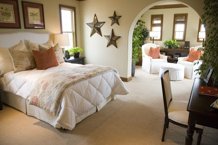 Bright, carpeted master bedroom with arch divide, copper star wall accents, white bedding and minimal accenting with salmon pillows.