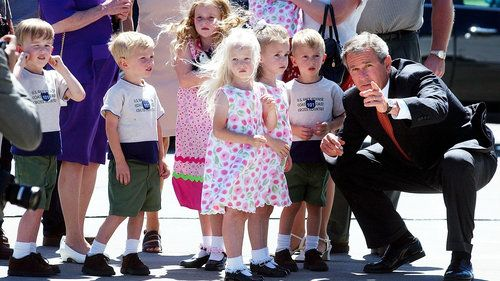 President Bush points out reporters and photographers to some of the McCaughey septuplets as they greet him at the Des Moines International Airport in Iowa in 2002.