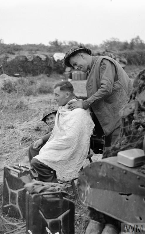 A soldier with the 1st Norfolk Regiment, 185th Infantry Brigade, 3rd Division, has a haircut in the line south of Venray, 16 October 1944.
