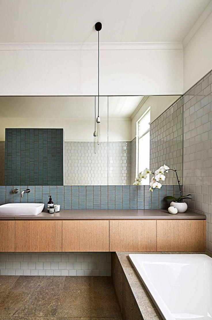 The large mirror,the different tiles, the grey, green and brown color sheme, the long cubboards and the sink on top; everything just how I would want it!