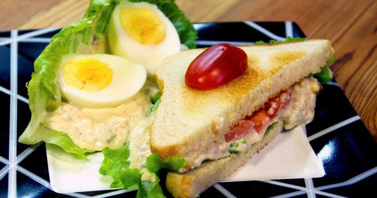 Krämig tonfiskröra med ägg, cheddar, och bostongurka serverad på bröd med skivade tomater och sallad.