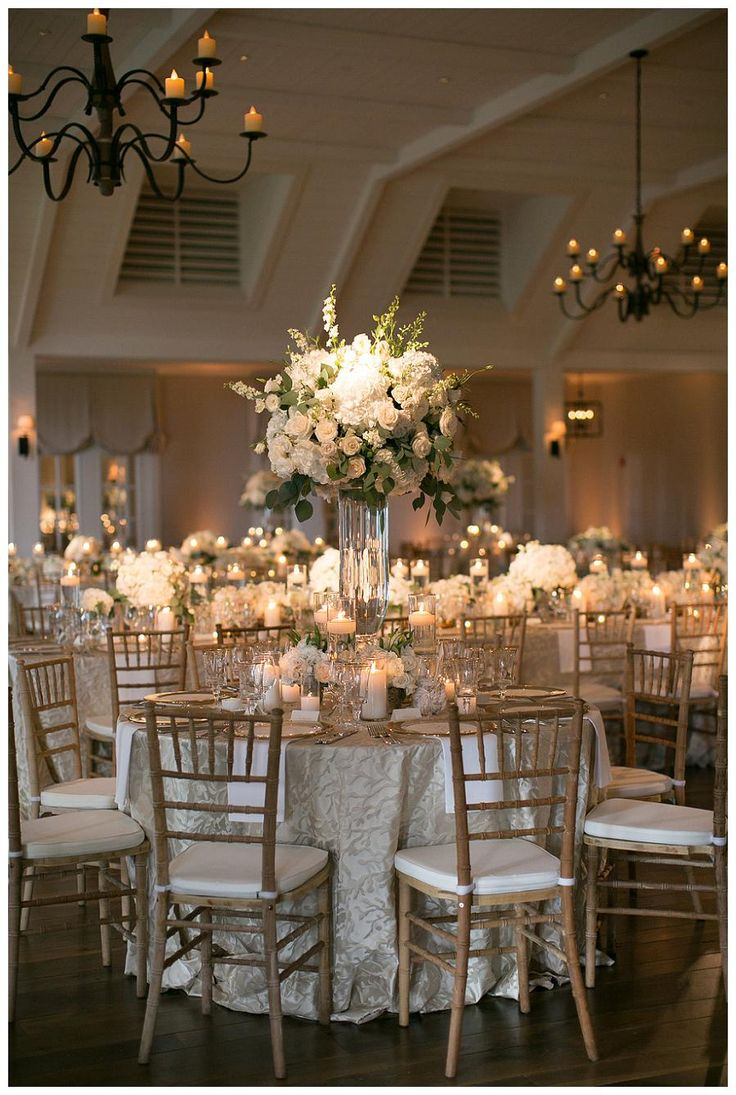 Gold, ivory and white wedding reception decor with white florals in glass vessels, place settings of gold-rimmed crystal and gold-rimmed glass chargers, floating candles, textured linens and natural wooden chairs. Event design and florals by Bella Flora,