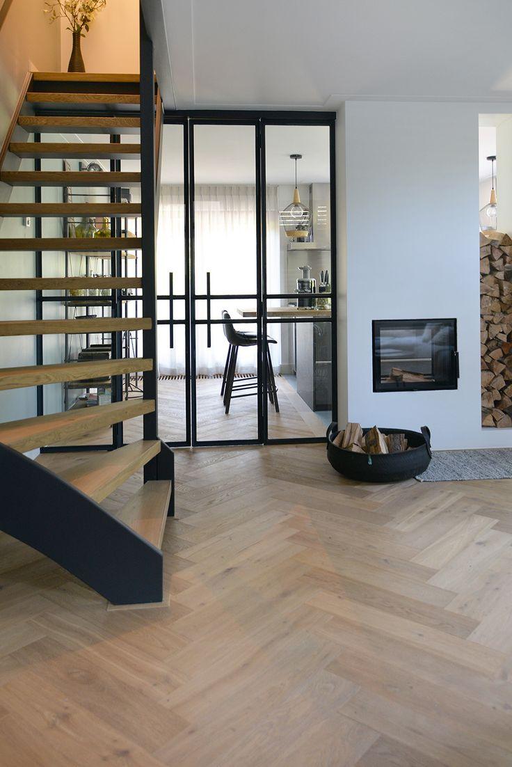 De visgraat vloer en openhaard met houtopslag zorgen voor een warme sfeer in de woonkamer. Het staal van de stalen deuren met glas, komt terug in de afwerking van de trap en geeft de ruimte een stoere look.