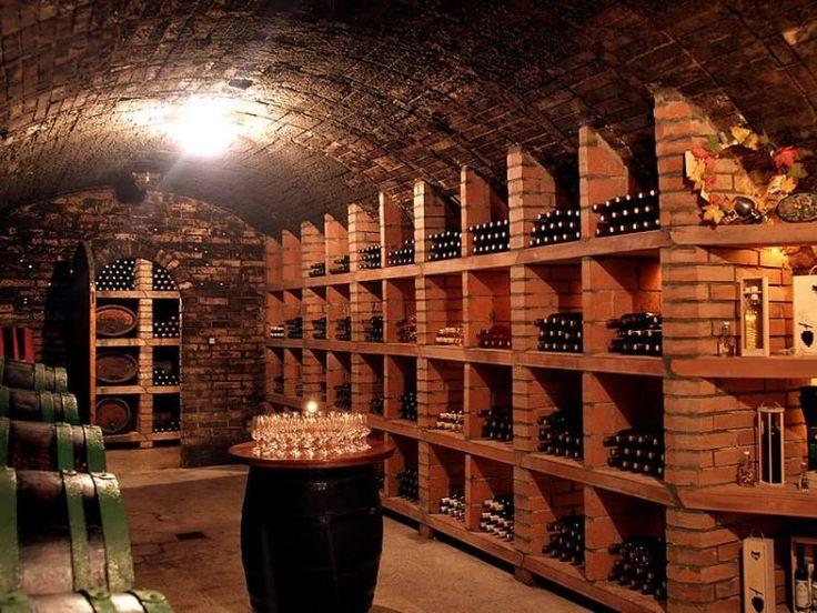 un support mural en brique rouge et une barrique dans la cave à vin