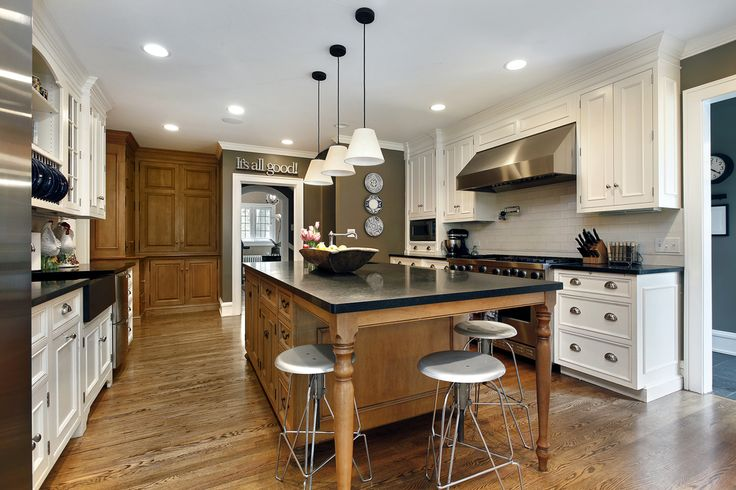 White White kitchen with dark counter tops and brown island. Ceiling is white and floor is natural wood.
