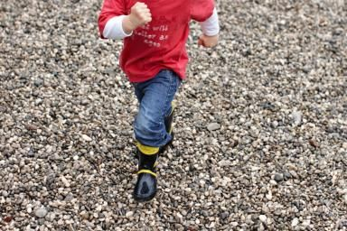 Toddler boy running on gravel - Cultura RM/Stephen Lux/Getty Images