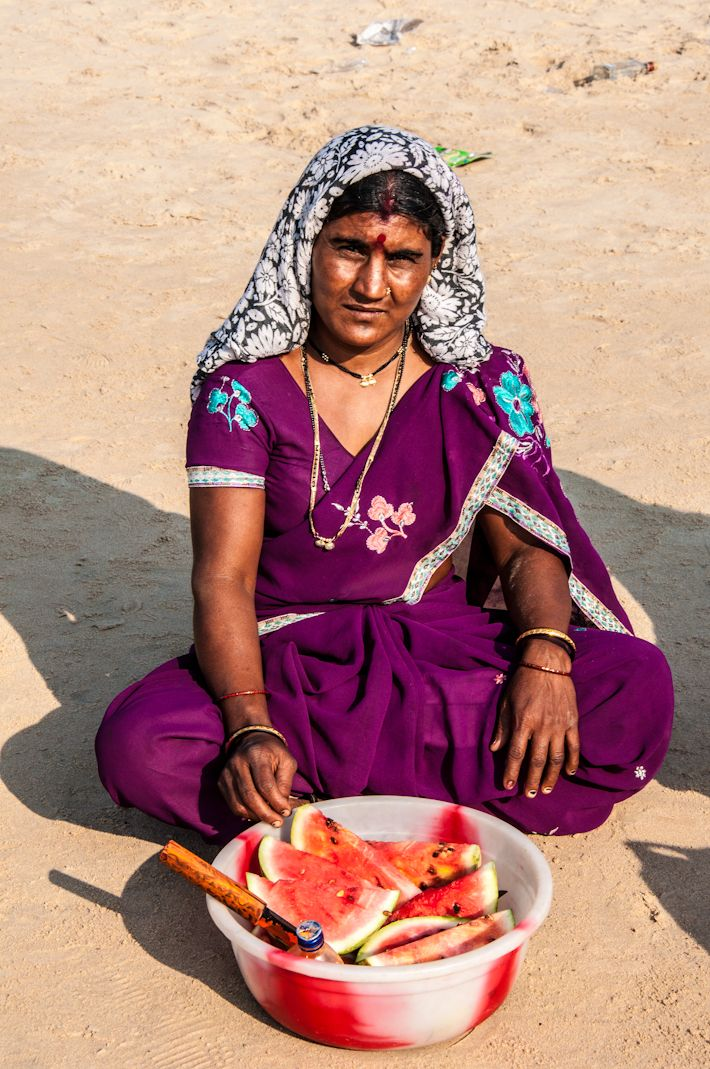 She makes a living selling watermelon slices at the beach in Goa, INDIA.