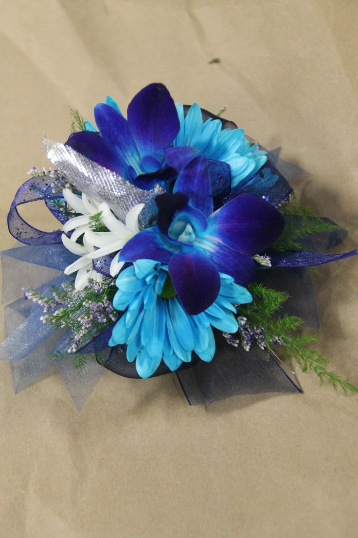 Blue dendro orchids & blue daisies, white hyacinths. Wrist corsage for prom or weddings, created by Judith Marie at Fox Bros Floral, Hartland, WI