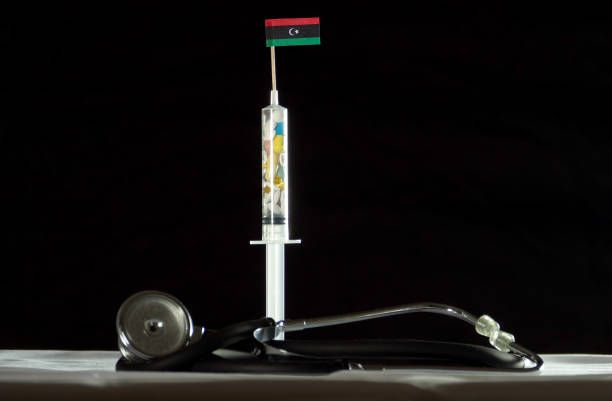 stethoscope and syringe filled with drugs injecting the libyan flag
