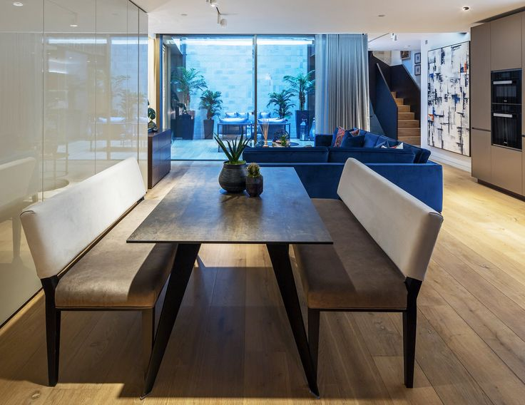 Clean and contemporary, this sleek bespoke bench in luxurious fabric adds another layer of crisp, linear alignment to our minimalist design of this Pathe Soho apartment dining area, the table echoing the organic oak feel of the flooring.