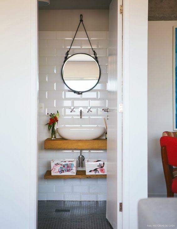 Lavabo tem revestimento subway e espelho redondo com faixa de couro.