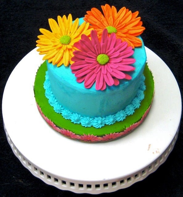 Shortbread cake filled with fresh strawberry cream filling.  Iced with cream cheese buttercream icing and decorated with handmade colored white chocolate Gerbera daisies.