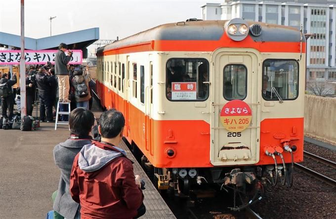 出発するキハ20系20型を見送る鉄道ファンら=19日、岡山県倉敷市