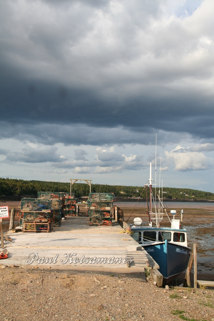 Stormy sky by dock at low tide