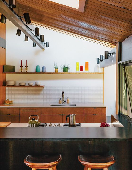 For the kitchen, master bath, and kids' bathroom, the designers chose three different hues of Savoy stacked mosaic tile from Portland-based manufacturer Ann Sacks. Tractor barstoolsby BassamFellows pull up to a PentalQuartz countertop. The gas cooktop, oven, and dishwasher are by Miele.