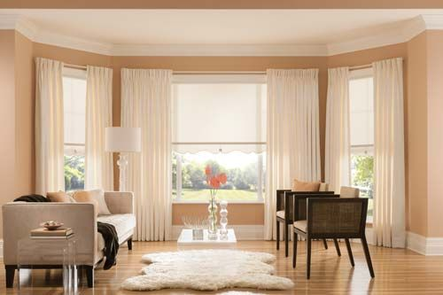 Create a serene environment by grouping shades, drapes, and wall color in the same like scheme of color.