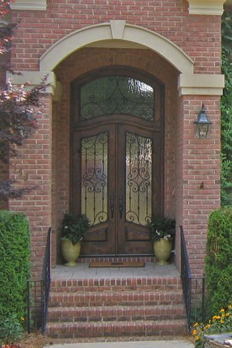 wood double entry door with wrought iron details and matching transom