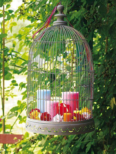 Einen antik anmutenden Vogelkäfig im Garten aufhängen. Mit farbigen Kerzen in unterschiedlichen Höhen und bunten Blüten dekorieren.