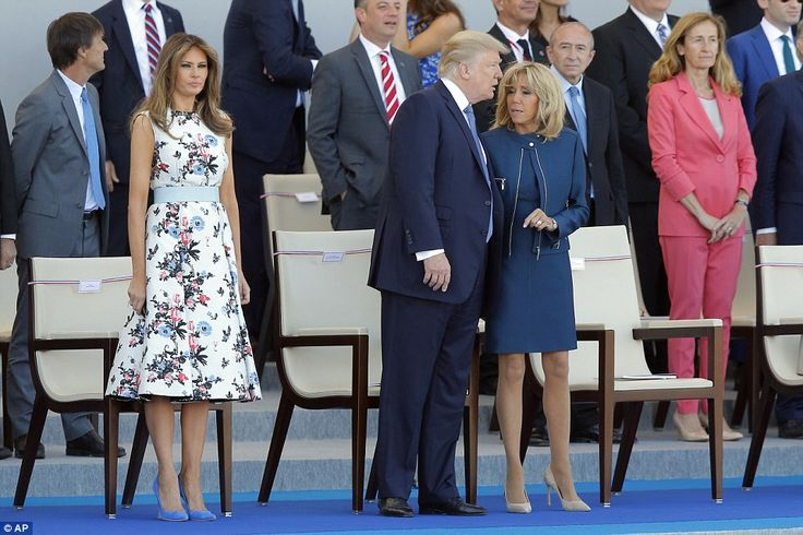 Cozy chats: Brigitte Macron, wife of French President Emmanuel Macron, talks to U.S. President Trump. First Lady Melania Trump, Paris, floral print white dress, blue shoes. July 14 2017