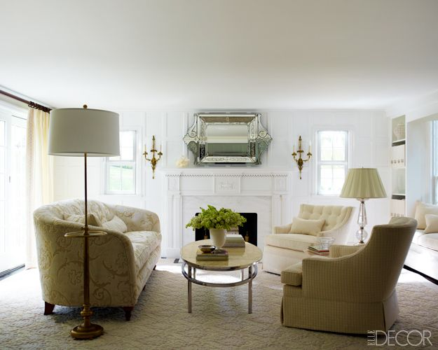 In the  living room, an antique sofa and a pair of chairs  by Jessica Charles; the floor lamp and Venetian mirror are antique, the mantel is by Forshaw, and the  rug is from Cornell Carpet & Design.   - ELLEDecor.com