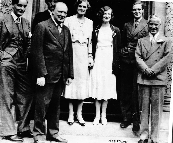 Tom Mitford with the Churchill family and Charles Chaplin. Tom is the first on the left, then Churchill, Freddie Birkenhead, Clementine Churchill, Diana Churchill, Randolph Churchill, and Chaplin. The photo is taken in Chartwell.