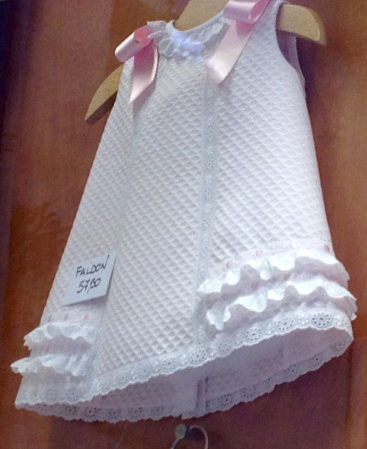 White sleeveless dress, trimmed with white lace and pink bows on shoulders, open at the back.  Pinned by AKT from Pinterest.