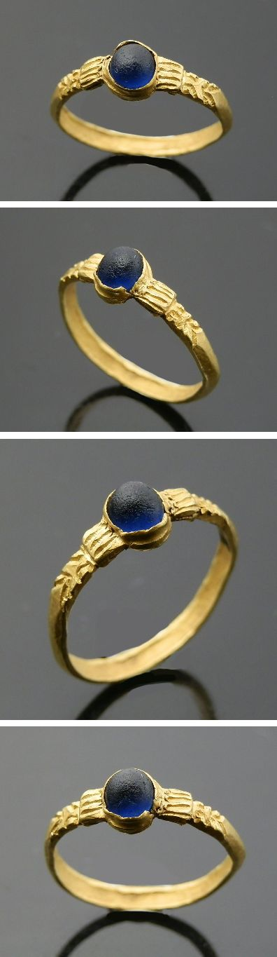 GOLD RING,    Shoulders decorated with stylized zoomorphic head leading to a raised blue glass set, Date: C. 12th-13th century .