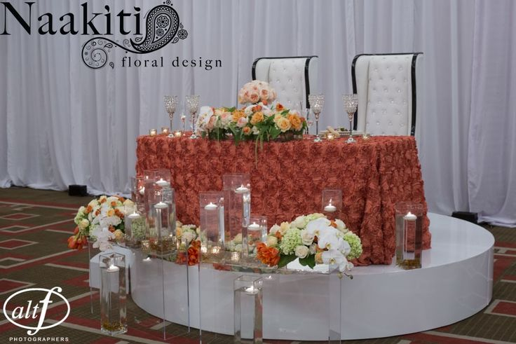 The sweetheart table was placed on top of our white round riser. The bride and groom sat in tufted white leather chairs. The floral on the table featured a long vase with peach garden roses, white roses, orange roses, orange tulips, green hanging amaranthus, and cream spray roses. #altfphotography #naakitifloral