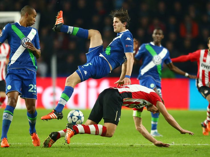 PSV's Luuk de Jong, bottom, and Wolfsburg's Timm Klose challenge for the ball during their Champions League Group B soccer match in Eindhoven, Netherlands.  Peter Dejong, AP