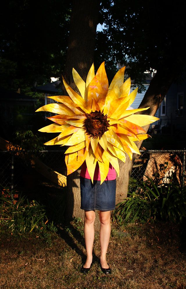 Make a giant paper sunflower with the following supplies that you can find at the Dollar Store: thick brown craft paper, multiple colors of latex paint (leftover house paint does just fine), hot glue gun, one platter size lightweight/paper plate, and one dinner size lightweight/paper plate