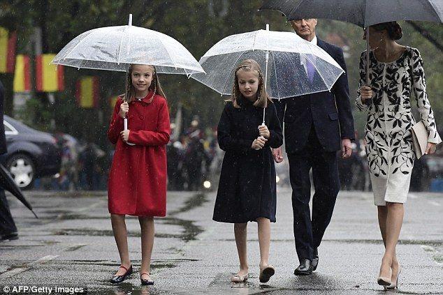 Style runs in the family: Letizia's two mini-me daughters wore matching wool coats in navy...