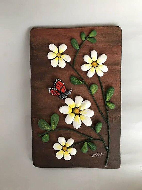 quadro floreale interamente realizzato a mano. la base è sagomata a mano in legno. le decorazioni sono realizzate in sassi dipinti. ogni pezzo è un pezzo unico. Misure : 18x28 cm