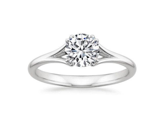 ''Pura''  Solitaire Diamond Engagement Ring At once feminine and contemporary, this ring divides into graceful ribbons of precious metal that intertwine and embrace the center diamond, securing it with split claw prongs.