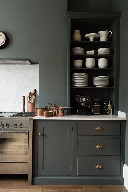 Gorgeous deep gray painted kitchen cabinets and walls with the inner cupboards painted black and brass hardware, copper pans and white marble countertop and backsplash to balance out the dark.