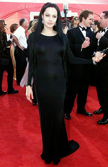 AT THE OSCARS - March 26, 2000 - March 26, 2000 Morticia Addams, is that you? Not only did she kiss her brother on the red carpet at the 2000 Academy Awards and pick up her first Oscar (for Best Supporting Actress in Girl, Interrupted), but a goth Angelina Jolie also made a statement in a long-sleeved black Versace gown and long black hair extensions.