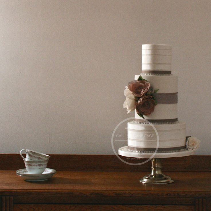 Banded in beige and ivory ribbons and adorned with rose and ivory coloured sugar roses.
