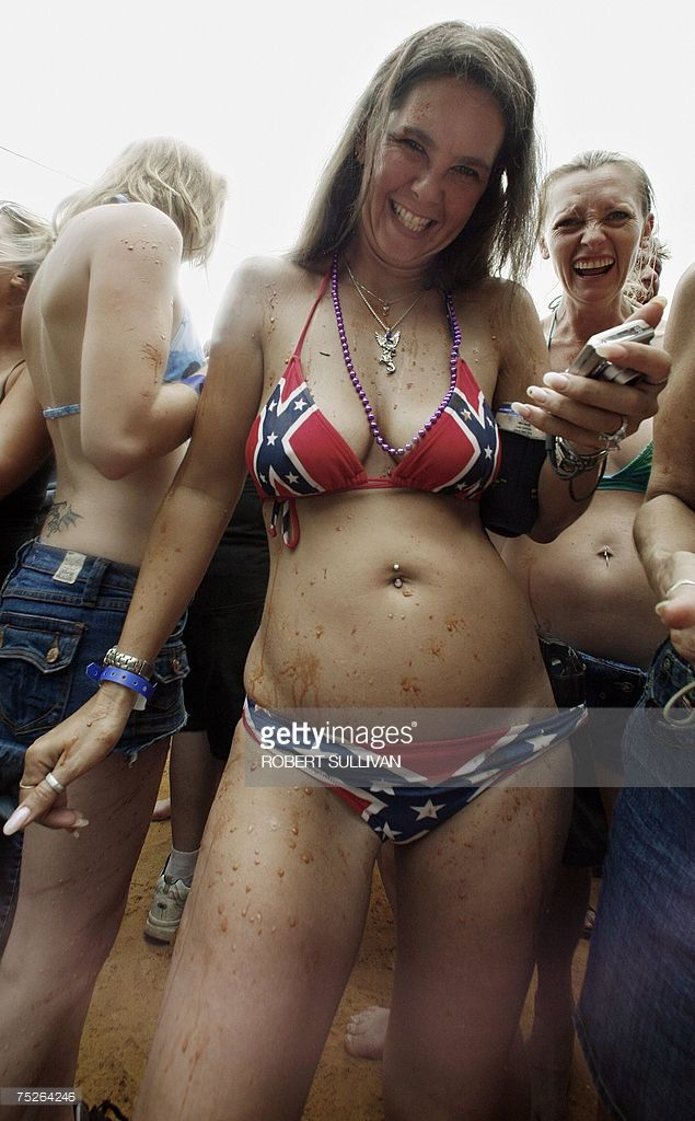 Rawni White of Warner Robins, Georgia, laughs after being splashed with mud on her Confederate flag bikini 07 July 2007 during the Mud Pit Belly Flop competition at the 2007 Redneck Games in East Dublin, Georgia. The day-long yearly festival celebrates the southern 'redneck' way of life.          AFP PHOTO/Robert SULLIVAN (Photo credit should read ROBERT SULLIVAN/AFP/Getty Images)