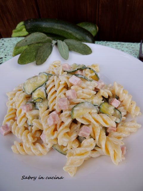 Pasta zucchine, panna e prosciutto  350 g short pasta penne type 150 g cooked ham in one piece a Zucchini 200 ml whipping cream salt freshly ground black pepper grated nutmeg a knob of butter 100 gr of grated Parmesan cheese