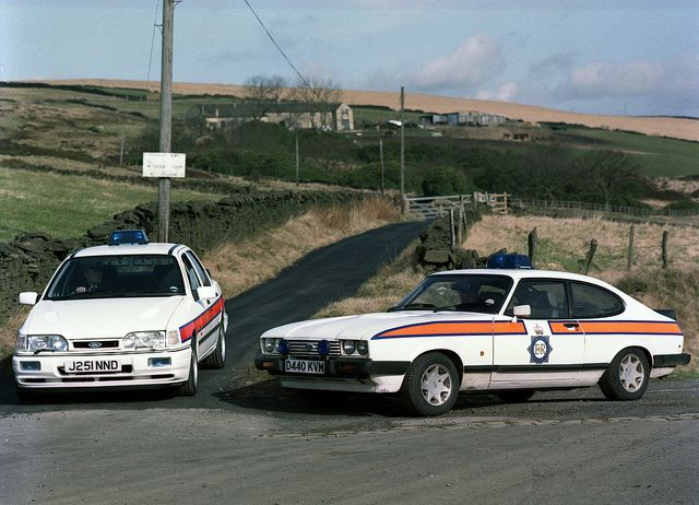 The last Ford Capri to see service with Greater Manchester Police stands alongside the Ford Sierra Cosworth that replaced it. This image is one of a series taken on Monday, 13 April, 1992, to mark the end of the of the Capri as a police vehicle in Manchester. The model was in service with the Force for many years and was the most iconic GMP car of its era. www.gmp.police.uk