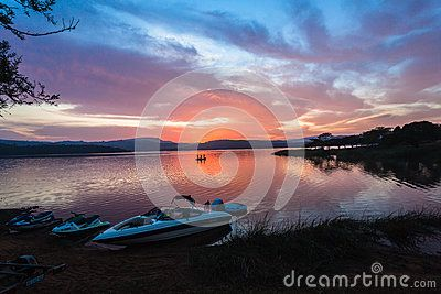 Dawn morning cloud colors water landscape on local dam with ski-boats on shoreline and distant bass fishing boat