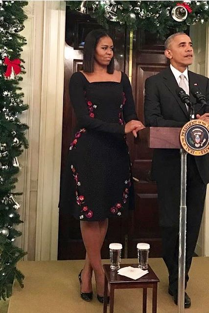 The First Lady wore a black Tanya Taylor dress featuring floral embroidery down the sides for her and President Obama's final holiday party at the White House.