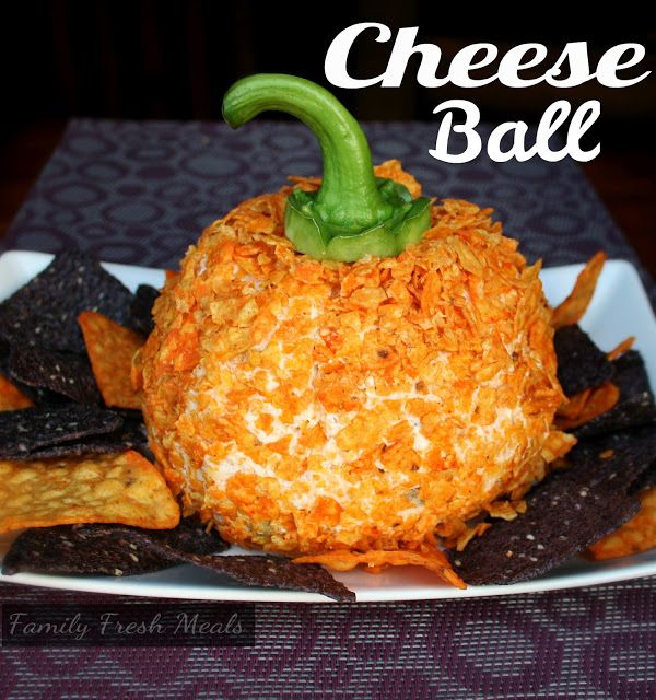 Dorito cheeseball that looks like an orange pumpkin or jackolantern for Halloween with a green bell pepper stem for the top