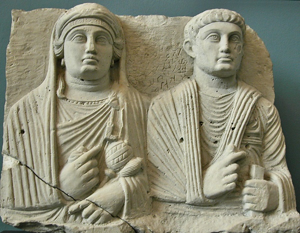 Couple on tombcover limestone The wife is veiled, wears a headband and is closely draped; she wears the symbols of her status as manager of the home: a key and 2 distaffs, one for wool and one for linen. The male is either a young husband or a son. Palmyra. 150 CE Copenhagen, Ny Carlsberg Glyptotek