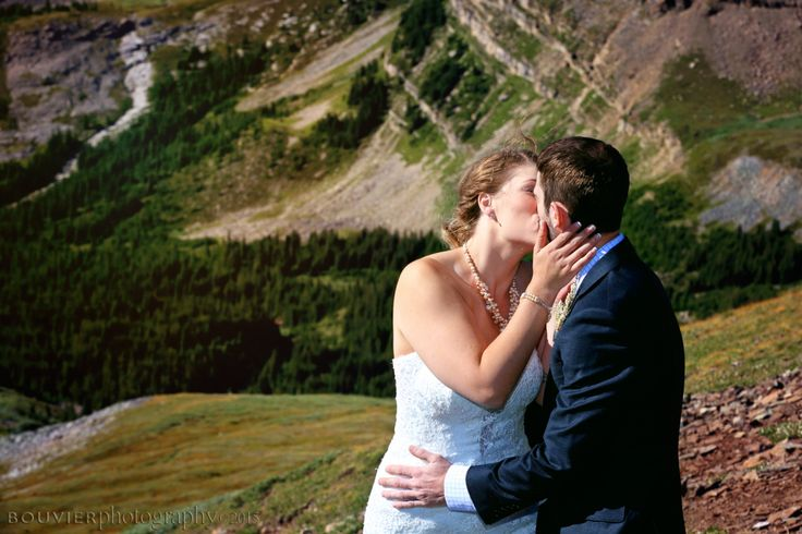 Bride & groom sharing a kiss on the mountain side in Canmore, Alberta. Summer heli-wedding. Canmore Alberta weddings.