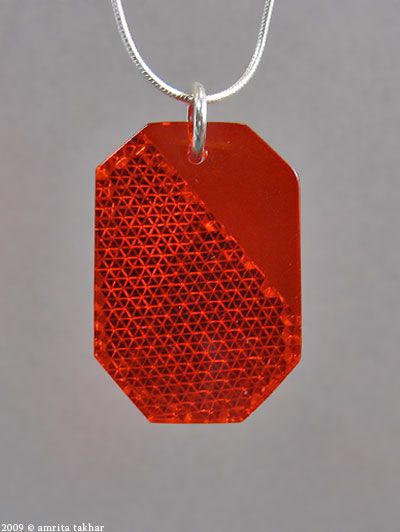 Reflect by AMRITA Broken tail light covers found at accident scenes and reflectors left on abandoned bike tires are used to make this light-catching jewelry.